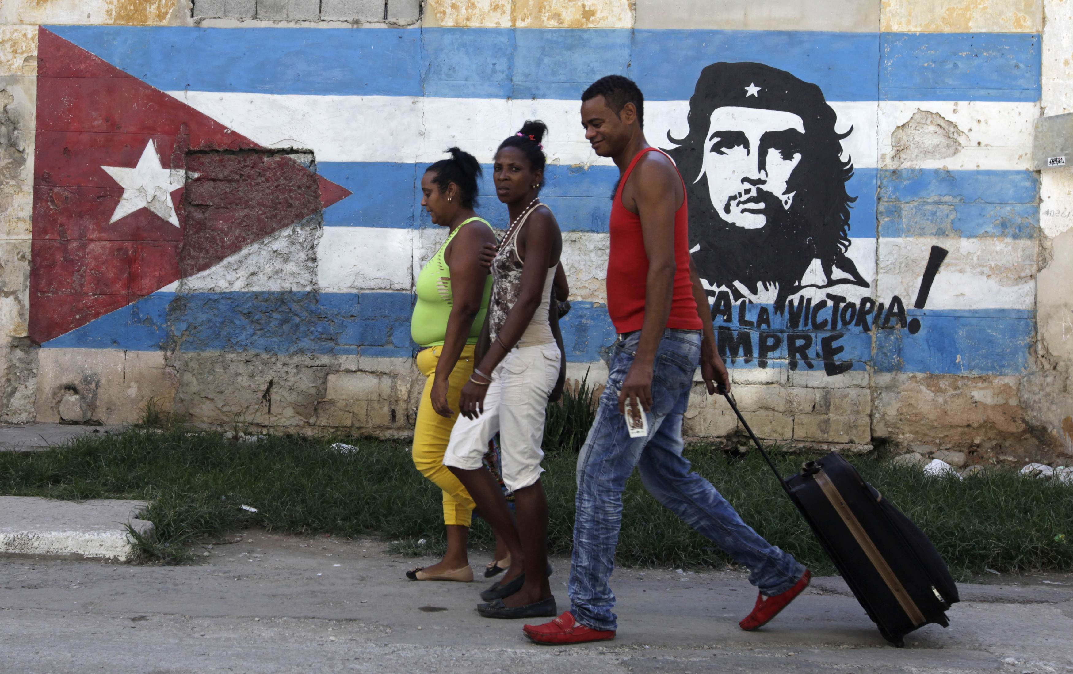 People walk beside a mural with images of rebel revolutionary leader Che Guevara and a Cuban flag in Havana